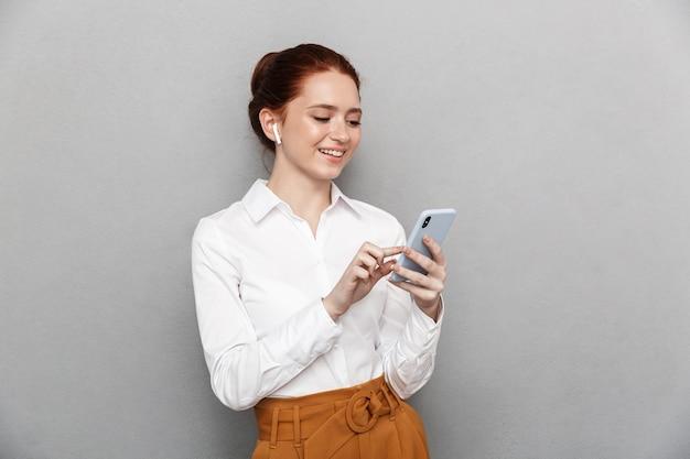 Ritratto di successo redhead imprenditrice 20s indossando auricolari tenendo e guardando lo smartphone in ufficio isolato su gray