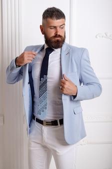 Ritratto di uomo d'affari sexy di successo maschio, barba lunga. modello di uomo barbuto elegante bello in posa indossando abito blu.