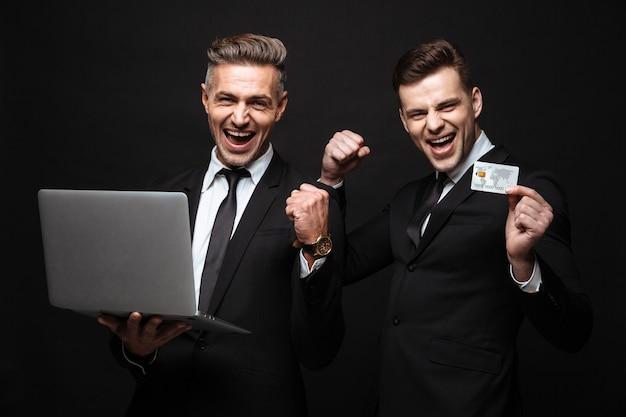 Ritratto di successo di due uomini d'affari vestiti con abiti formali che celebrano mentre si tiene in mano un laptop e una carta di credito isolati su un muro nero