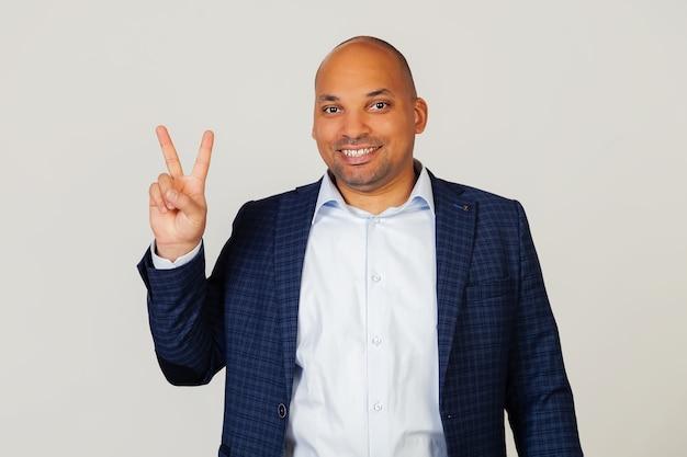 Ritratto di un giovane uomo d'affari afroamericano di successo, mostrando con le dita al numero due, sorridente, fiducioso e felice. l'uomo mostra due dita. numero 2.