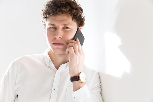 Ritratto di un giovane uomo d'affari dai capelli ricci attraente di successo in piedi davanti al muro bianco, parlando al cellulare
