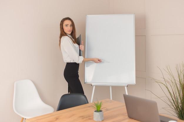 Ritratto di un giovane imprenditore di successo in piedi vicino alla lavagna in ufficio tiene una presentazione