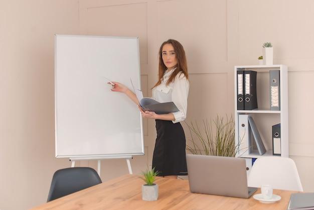 Ritratto di giovane imprenditore di successo in piedi vicino alla lavagna in ufficio tiene riunione