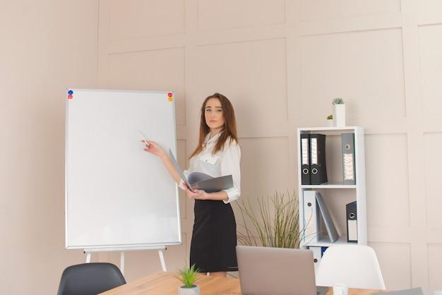 Ritratto di giovane imprenditore di successo in piedi vicino alla lavagna in ufficio