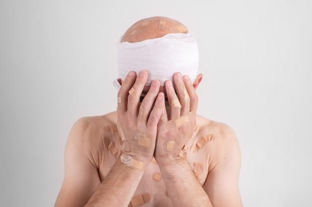 Ritratto di uomo malato con la testa bendata sentirsi male e copre il viso con le mani.