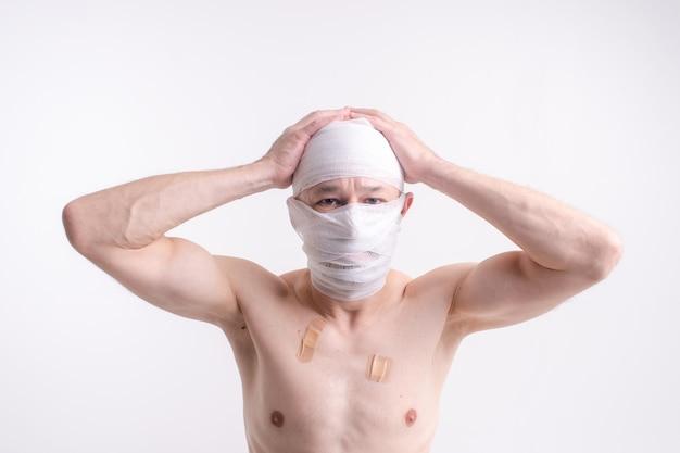 Ritratto di uomo malato con la testa bendata sentirsi male.