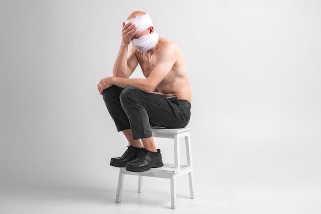 Il ritratto del maschio del malato con la testa bendata si siede su una sedia.