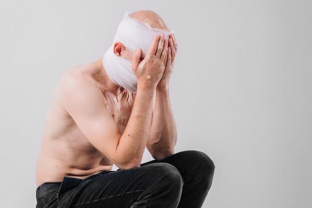 Ritratto di uomo sofferente con la testa bendata che copre il viso con le nads.