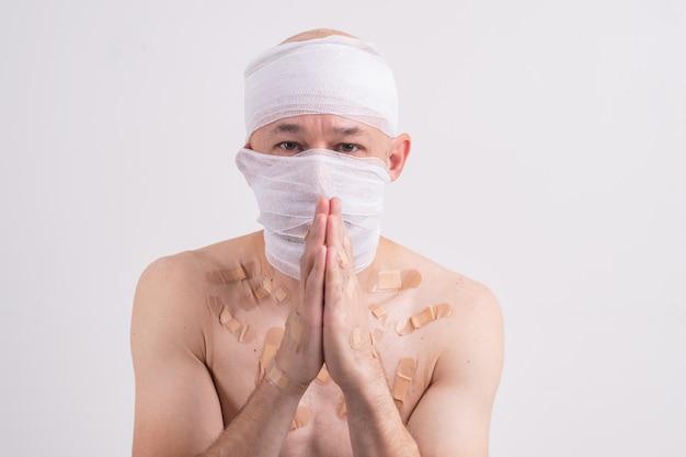 Ritratto di un uomo sofferente con la testa bendata che si sente male e chiede di aiutare.