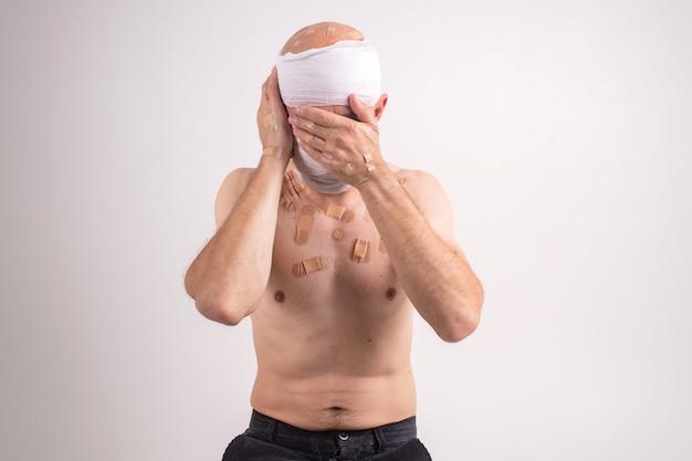 Ritratto di uomo sofferente con la testa bendata sentirsi male e copre il viso con le mani
