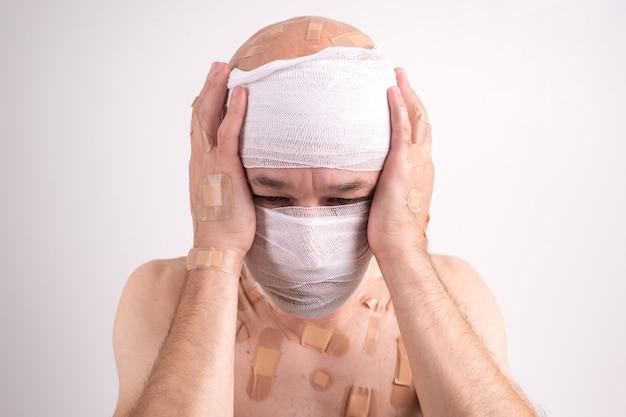Ritratto di uomo sofferente con la testa bendata sentirsi male e si copre le mani sulle orecchie