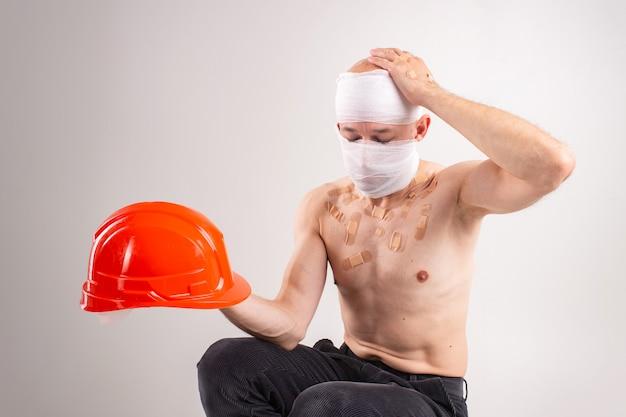 Ritratto del maschio sofferente con la testa bendata e molte toppe sul suo corpo tenendo in mano il casco