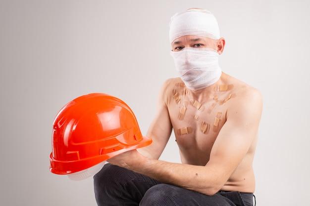 Ritratto di uomo sofferente con la testa bendata e molte toppe sul suo corpo con casco in mano