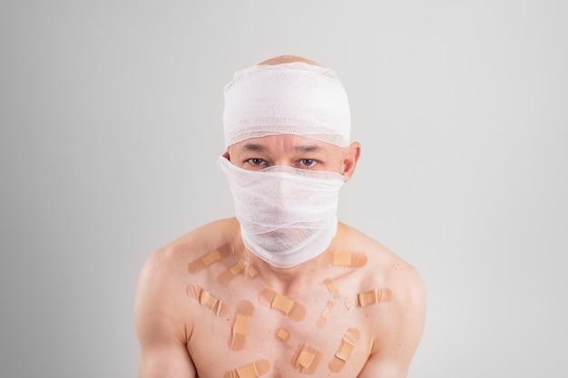 Ritratto di uomo sofferente con la testa bendata e molte toppe sul suo corpo