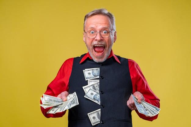 Ritratto di un uomo maturo anziano super eccitato che ha appena vinto un sacco di soldi, cercando di dare soldi alla telecamera, isolato su sfondo giallo. sentimenti di espressione facciale di emozione positiva. avvicinamento