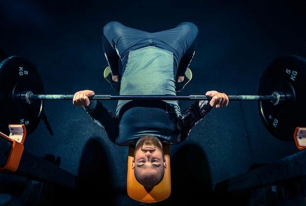 Ritratto di un giovane muscoloso in ottima forma che si allena in palestra con bilanciere su blue