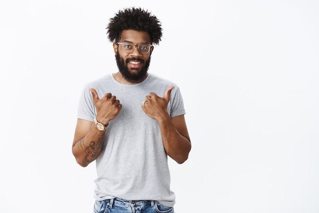Ritratto di supporto di bell'aspetto soddisfatto fidanzato afroamericano con tatuaggi, naso trafitto e barba che mostra gesto di pollice in su e sorridente in allegria felice per l'amico