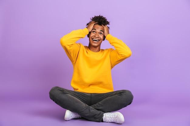 Ritratto di un ragazzo afroamericano sorpreso che grida e afferra la testa mentre è seduto sul pavimento con le gambe incrociate, isolato su sfondo viola