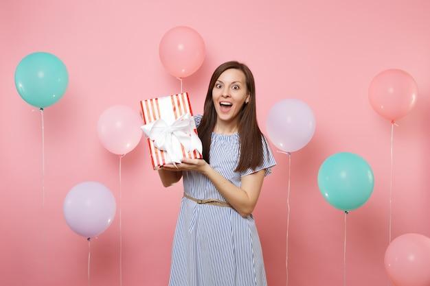 Ritratto di una giovane donna sorpresa sorpresa in abito blu che tiene in mano una scatola rossa con un regalo presente su sfondo rosa pastello con mongolfiere colorate. festa di compleanno, concetto di emozioni sincere della gente.