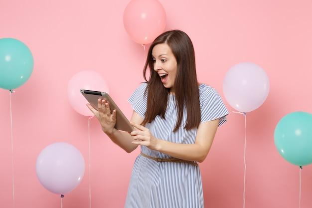 Ritratto di bella donna sorpresa che indossa un abito blu che tiene utilizzando il computer tablet pc su sfondo rosa pastello con mongolfiere colorate. festa di compleanno, concetto di emozioni sincere della gente.