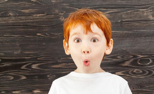 Ritratto di un bambino sorpreso con capelli rossi, lentiggini e occhi marroni, su uno sfondo nero