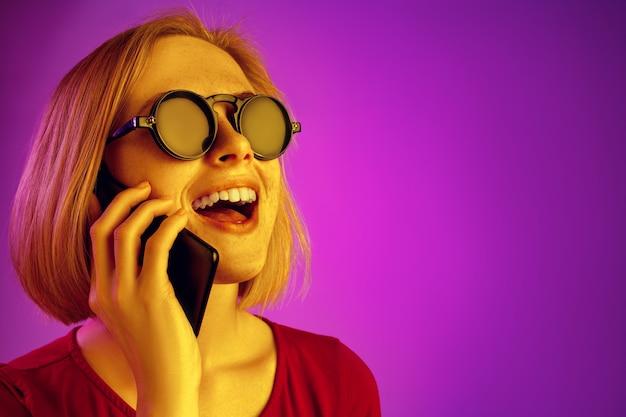 Ritratto di donna sorpresa confusa che guarda il telefono cellulare isolato su sfondo al neon rosa