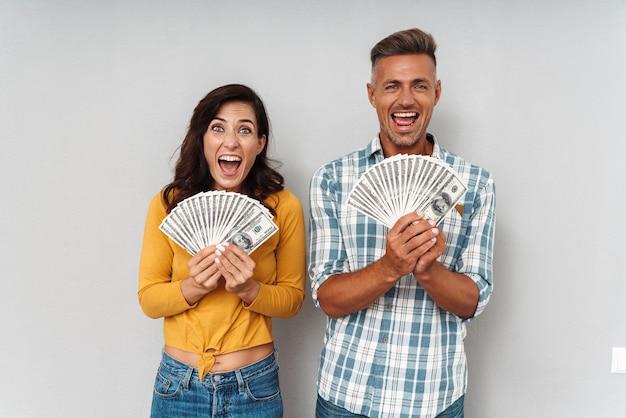 Ritratto di una coppia amorosa adulta emotiva sorpresa che tiene soldi isolati sopra il muro grigio