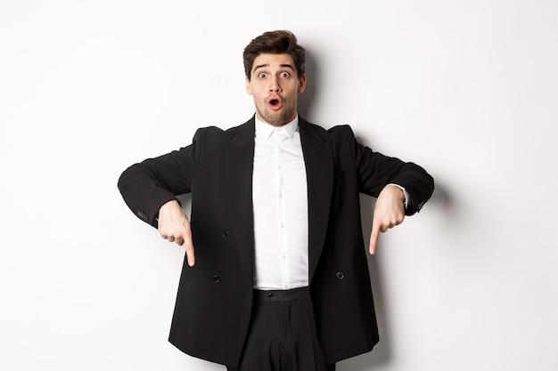 Ritratto di un uomo sorpreso ed eccitato in abito nero, che punta le dita verso il basso e mostra la pubblicità di natale, in piedi su sfondo bianco