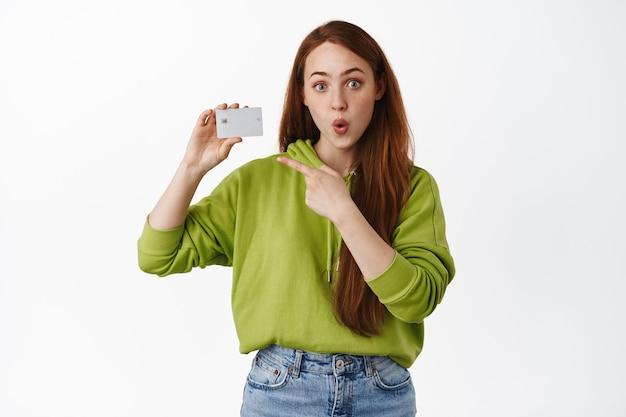 Ritratto di una ragazza sorpresa allo zenzero che parla di banca o di sconti, puntando il dito sulla carta di credito e fissando stupita sul bianco