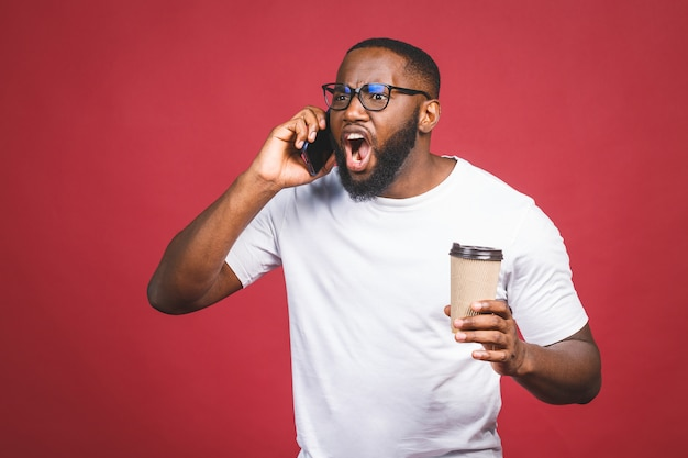 Il ritratto dell'uomo afroamericano bello sorpreso con il telefono cellulare e porta via la tazza di caffè. isolato su sfondo rosso.