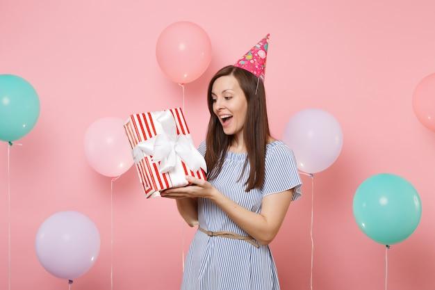 Ritratto di giovane donna felice sorpresa in abito blu cappello compleanno tenere scatola rossa con regalo presente su sfondo rosa pastello con palloncini colorati. festa di compleanno, persone sincere emozioni.