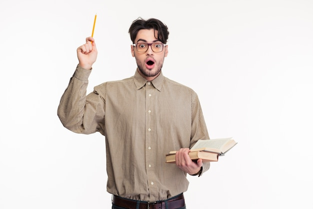 Ritratto di un uomo sorpreso in piedi con un libro isolato su un muro bianco