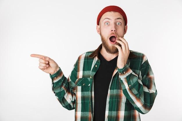 Ritratto di uomo sorpreso che indossa un cappello e camicia a quadri ridendo e puntando il dito da parte, mentre in piedi isolato su sfondo bianco
