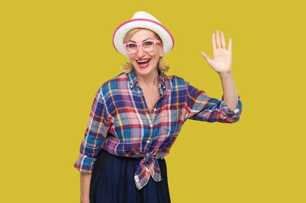 Ritratto di donna matura elegante moderna sorpresa in stile casual con cappello e occhiali in piedi agitando la mano e guardando la telecamera con un sorriso a trentadue denti. girato in studio isolato su sfondo giallo.