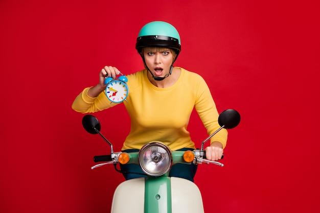 Ritratto di sorpresa negativa ragazza giro in moto tenere la bocca aperta dell'orologio