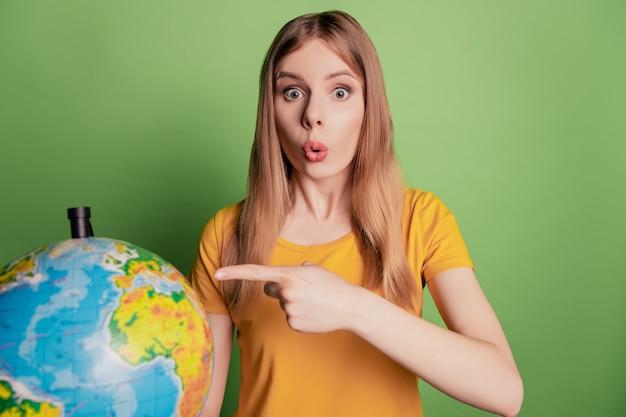 Ritratto di sorpresa omg reazione signora diretta indice globo continente indossare occhiali da sole t-shirt gialla