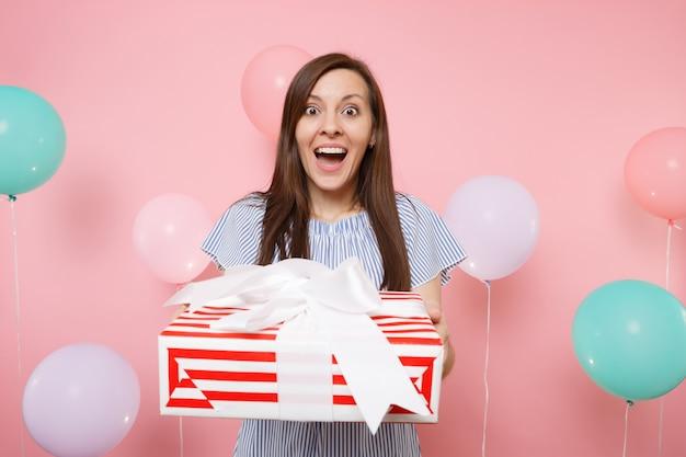 Ritratto di una bella giovane donna sorpresa in abito blu che tiene in mano una scatola rossa con un regalo presente su sfondo rosa pastello con mongolfiere colorate. festa di compleanno, concetto di emozioni sincere della gente.