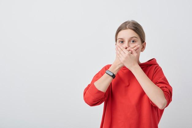 Ritratto di ragazza adolescente sorpresa in felpa con cappuccio che copre la bocca con le mani per l'eccitazione