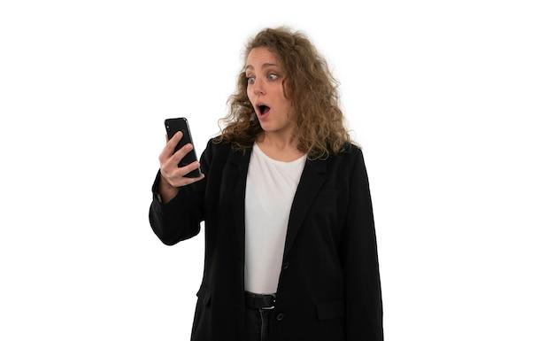 Ritratto di una donna sorpresa che tiene lo smartphone in mano. concetto di vincere un premio o vincere denaro online, isolato su sfondo bianco.