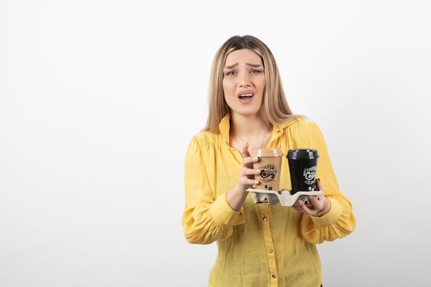 Ritratto di donna sorpresa in posa con tazze di caffè su bianco.
