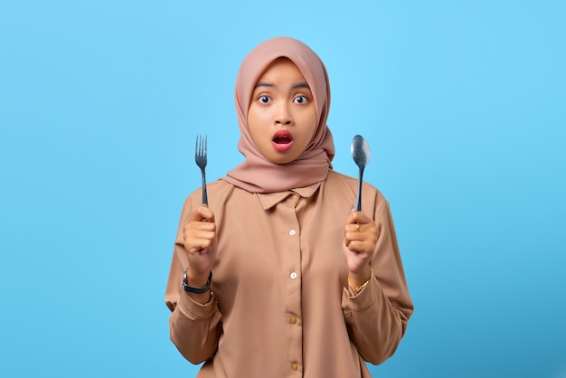 Ritratto di una giovane donna asiatica sorpresa tiene forchetta e cucchiaio con la bocca aperta su sfondo blu