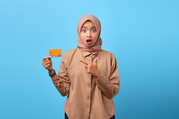 Ritratto di giovane donna asiatica sorpresa che indica sulla carta di credito sopra fondo blu