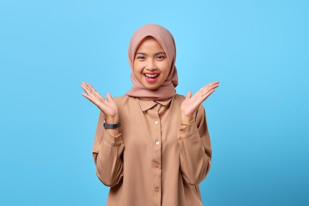 Ritratto di una giovane donna asiatica sorpresa ha alzato la mano con la bocca aperta su sfondo blu