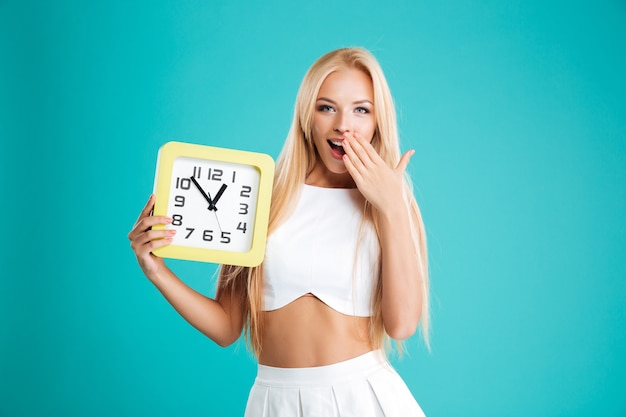 Ritratto di una ragazza sorpresa che tiene l'orologio da parete e copre la bocca aperta con il palmo isolato sullo sfondo blu
