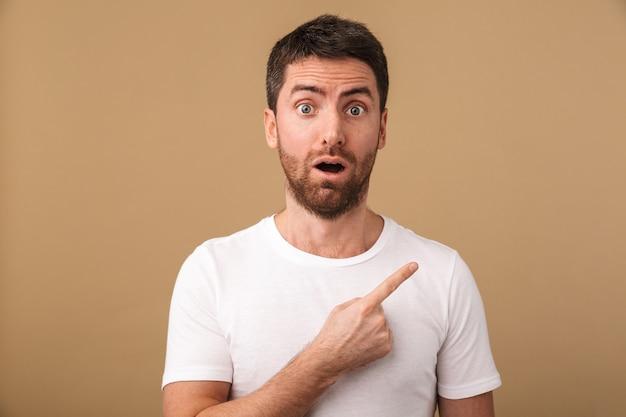 Ritratto di un giovane sorpreso vestito casualmente in piedi isolato su beige, indicando lo spazio della copia