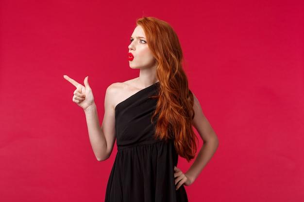 Ritratto di giovane donna rossa confusa sospettosa o incerta che fa domande su cose strane, indicando e guardando socchiudendo gli occhi nell'angolo in alto a sinistra, difficile vedere cosa ci