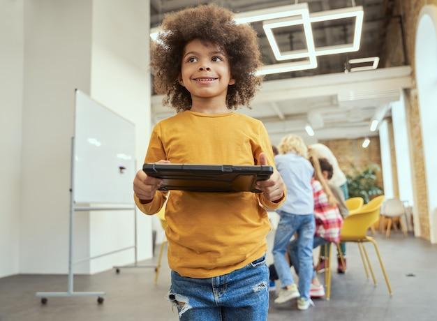 Ritratto di un dolce ragazzino con i capelli afro che guarda lontano tenendo in mano un tablet pc in piedi in un'aula
