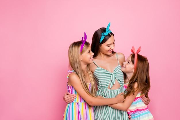 Ritratto di sorelle dolci abbracciando cercando indossando fasce di gonna abito luminoso isolato su sfondo rosa