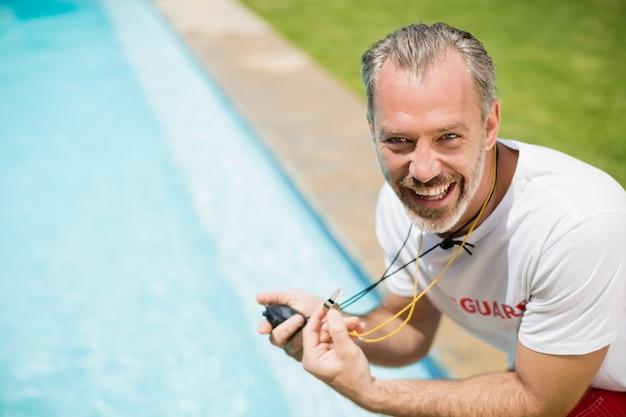 Ritratto di nuotare allenatore tenendo il cronometro vicino a bordo piscina