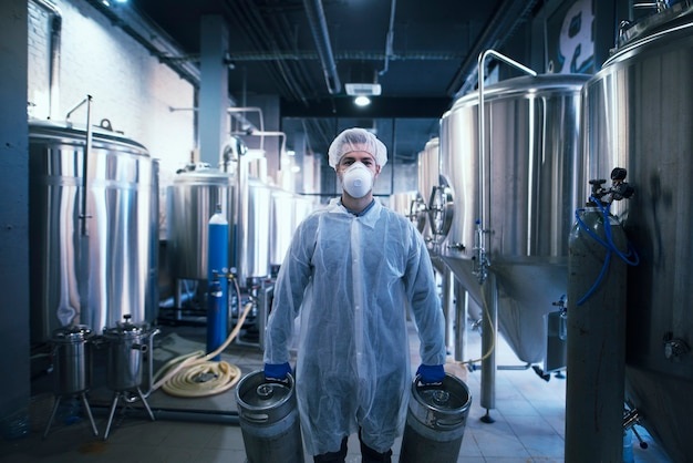 Ritratto di tecnologo in uniforme bianca con retina per capelli e maschera che tiene le bombole di gas in impianto per la produzione di alimenti o bevande.
